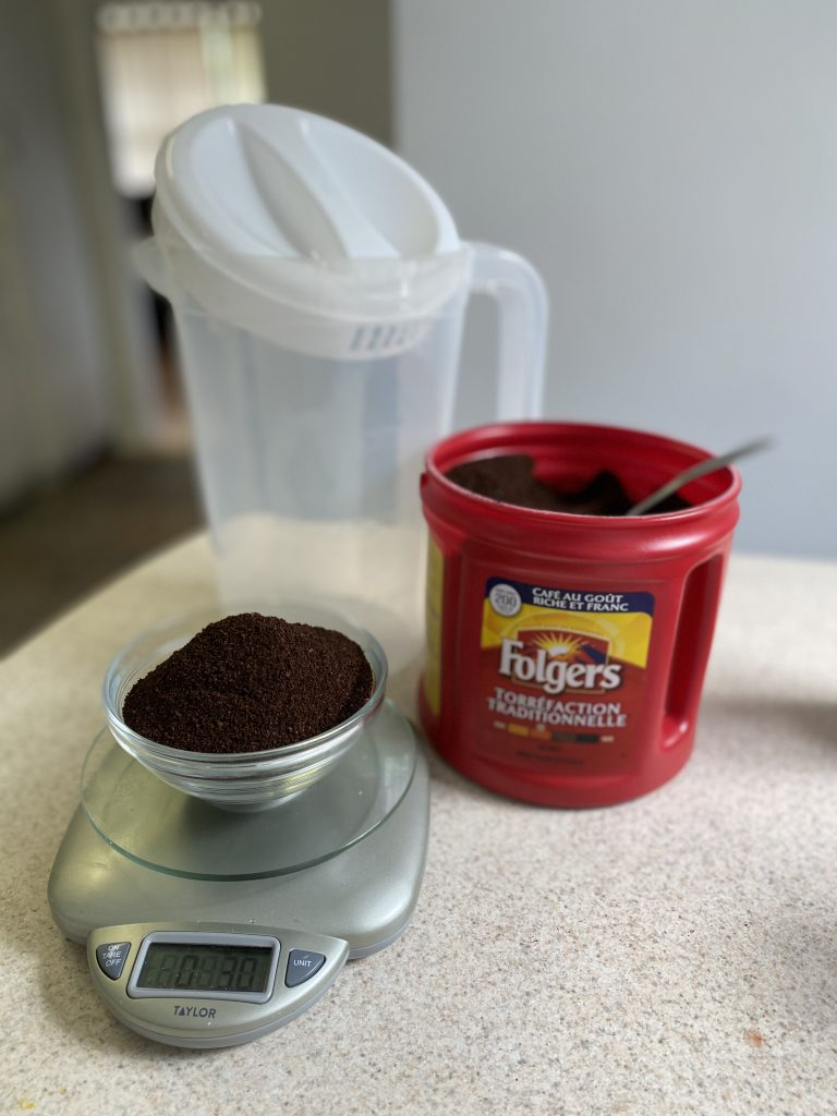 Preparing Coffee Grounds for homemade cold brew coffee, a scale, container and Folgers coffee are on a table