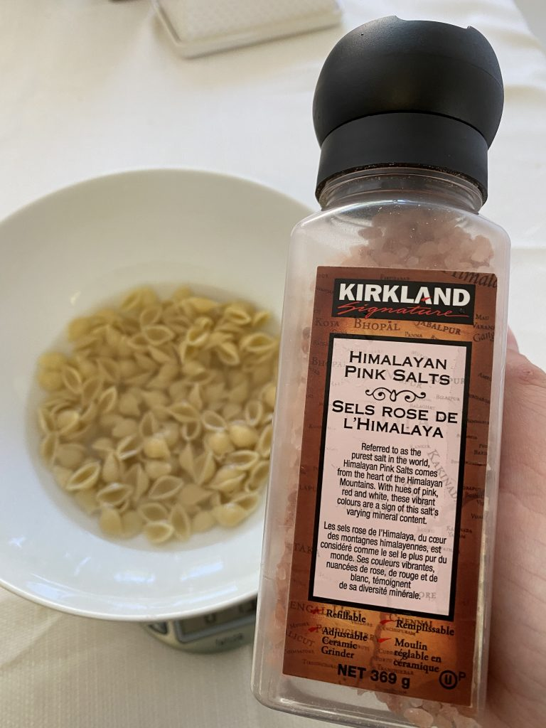 A bowl of noodles and water with a container of Kirkland salt in the forefront of the image.