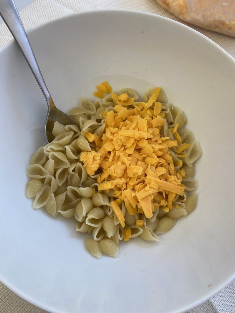 A bowl of cooked noodles topped with freshly grated cheddar cheese with a spoon on the left side of the bowl ready to mix the bowl's contents