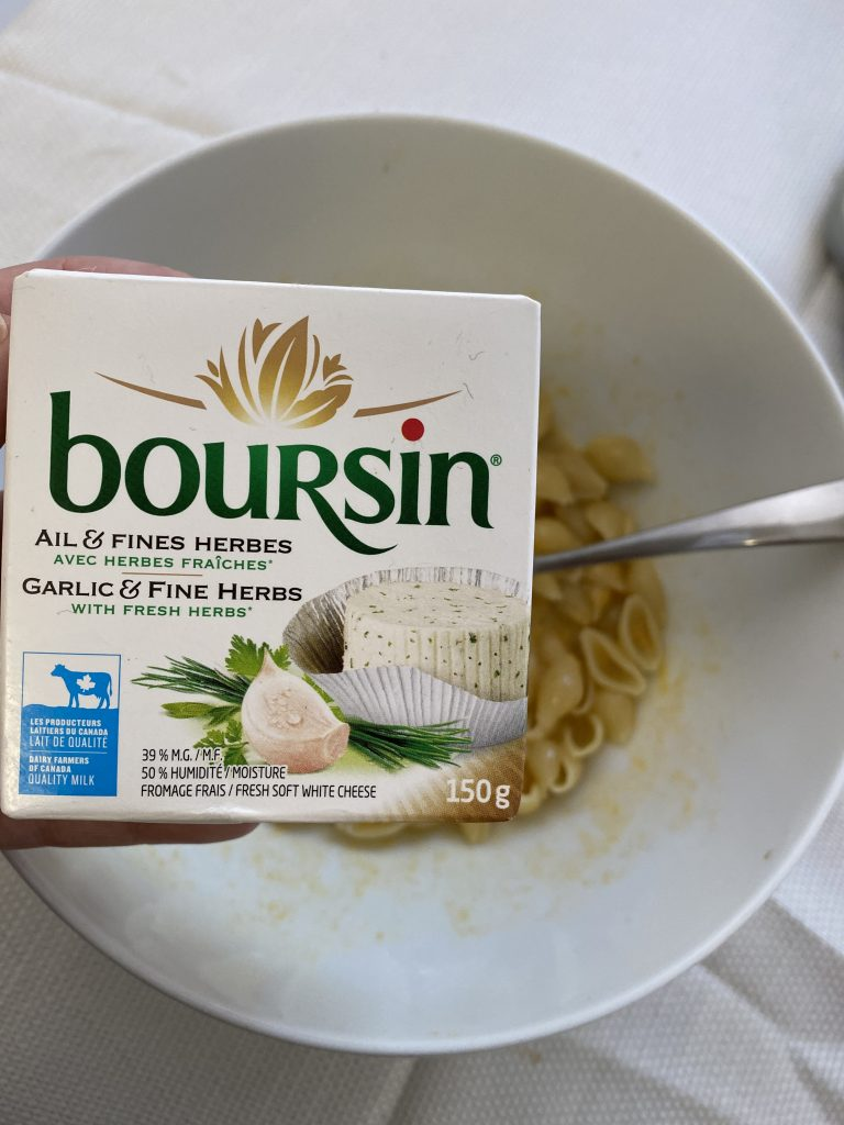 A box of Boursin Herb and Garlic Cheese being held over the bowl of cheesy noodles.